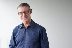 Portrait of happy senior man with dentures wearing glasses, smiling at camera