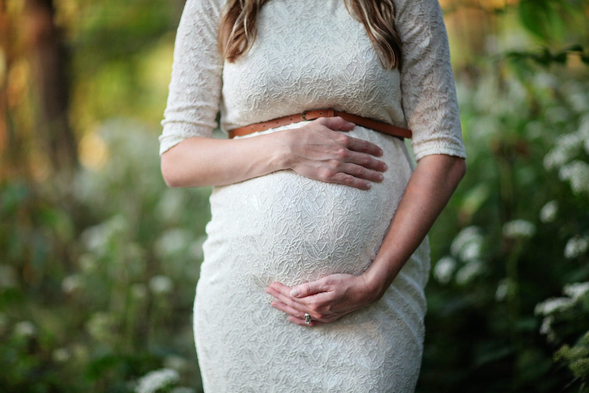 A pregnant woman holding her belly wondering if dentures are right for her or not