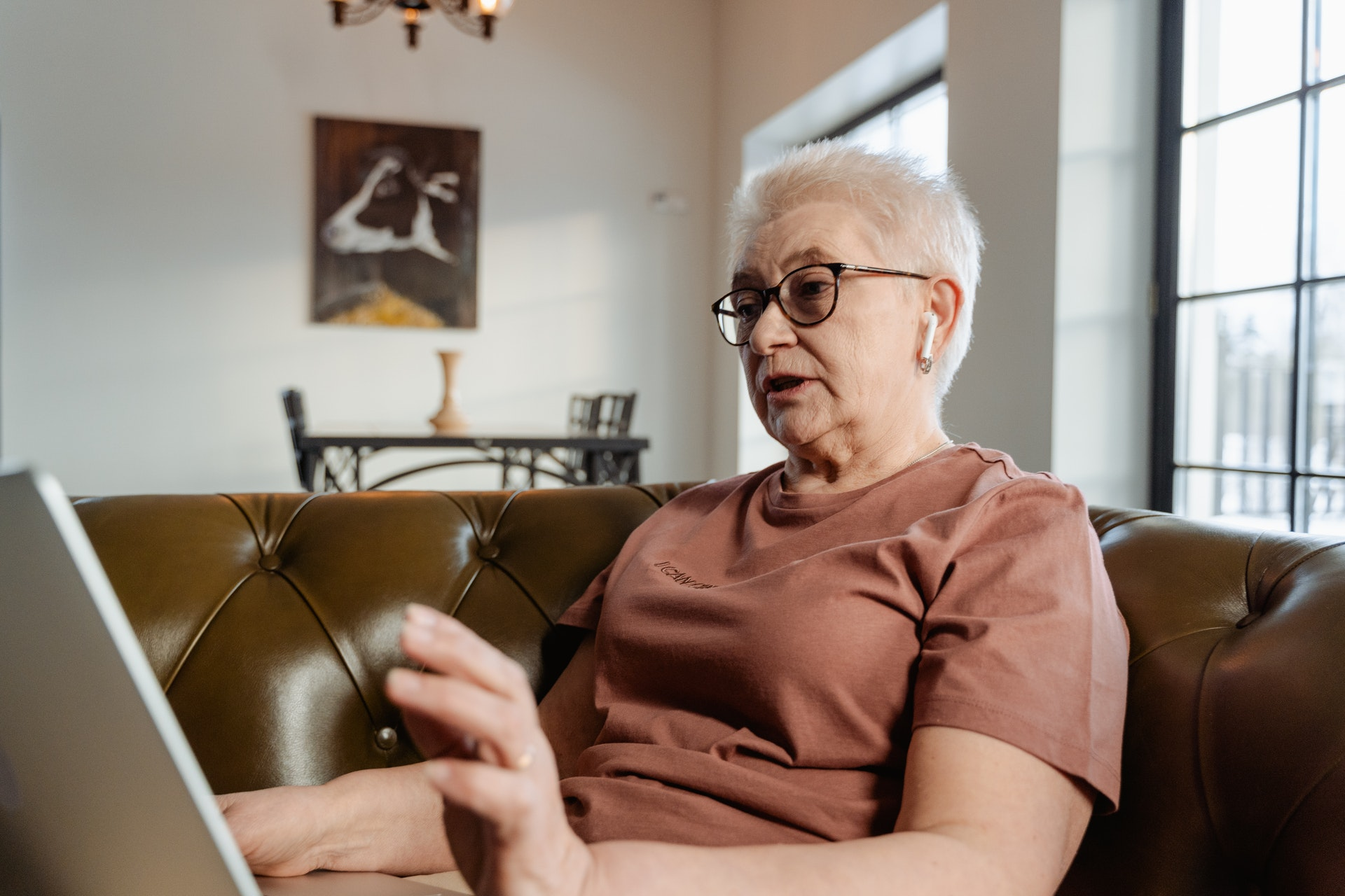 Senior woman on her laptop researching whether she should get dentures or dental implants in Surrey